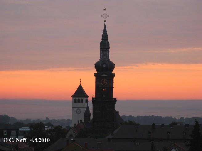 morgentlicher Blick auf St. Martin Grünstadt (ev.) - es ist 6.17 aber die Kirchturmuhr zeigt seit dem 6.6.2010 immer12 Uhr 17 an ! Im Hintergrund sieht man St. Peter (kath) mit der richtigen Uhrzeit, © C.Neff  4.8.2010